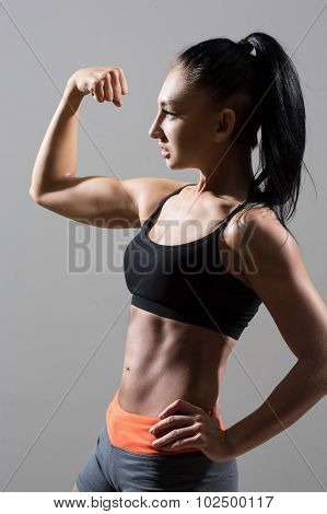 Portrait of young fitness woman shows biceps. Muscular female body with sweat. Perfect sportive female body. poster