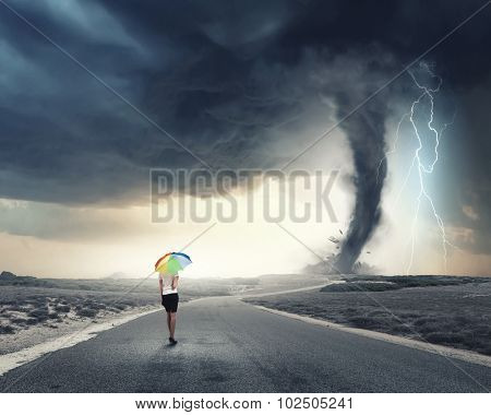 Young pretty businesswoman with rainbow colorful umbrella walking in storm
