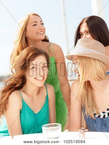 summer holidays and vacation concept - group of smiling girls in cafe on the beach