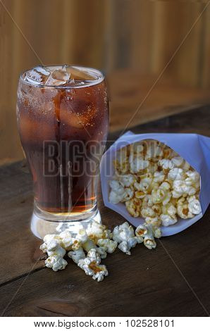 Cola in glass with popcorn on wood background.