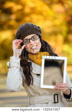 Woman With Glasses Showing Digital Tablet In Autumn