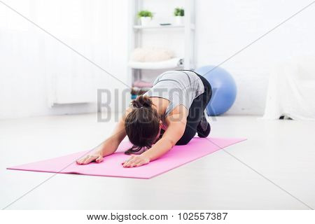 fit woman bending over on mat doing pilates exercise at home in the living room