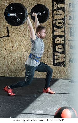 Young strong man doing weightlifting in the gym poster