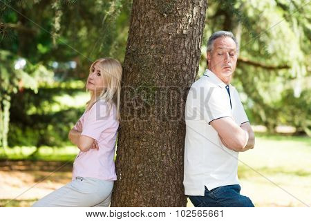 Mature couple standing against each other after a lovers tiff