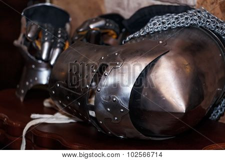 knight's helmet with visor and gloves on the table
