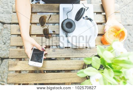 View Over A Table With A Composition Of Vegan Shake, Tablet,headset And Woman Hand Holding A Smart P