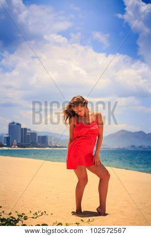 Blond Girl In Red Stands On Beach Smooths Shaken By Wind Hair
