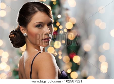 people, holidays, jewelry and luxury concept - woman face with diamond earring over christmas tree lights background