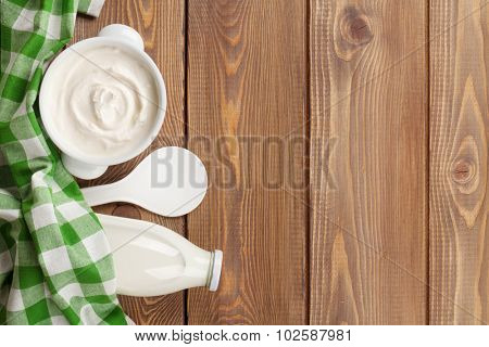 Sour cream in a bowl and milk bottle on wooden table. Top view with copy space