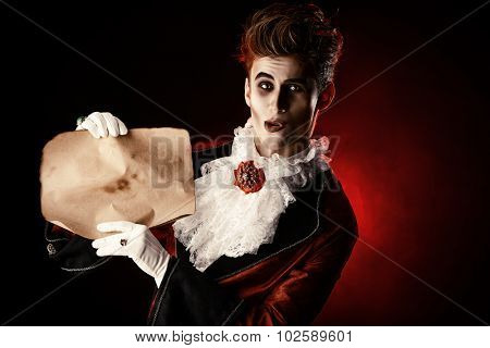 Attractive and frightening vampire holding a Sheepskin Scroll. Halloween. Dracula costume. poster