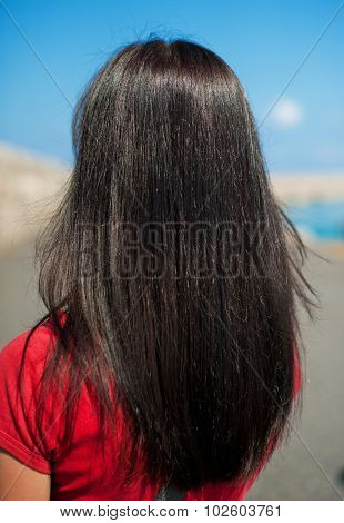 view of a young woman with long dark brown straight hair on the scenery