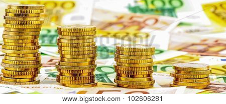 stack of money coins, falling curve symbol photo for falling interest rates and lower costs