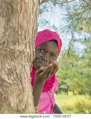 Afro girl sending a kiss from behind a filao tree, ten years old