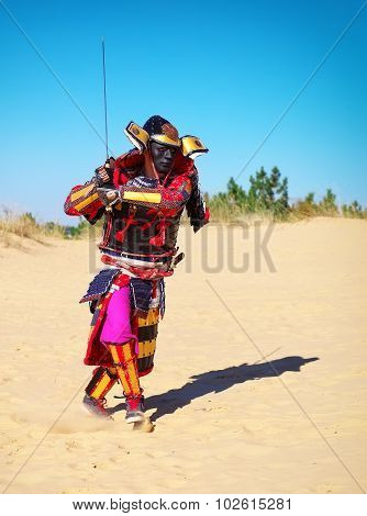 Man In Samurai Costume With Sword Running On The Sand. Men In Samurai Armour Running On The Sand. Or