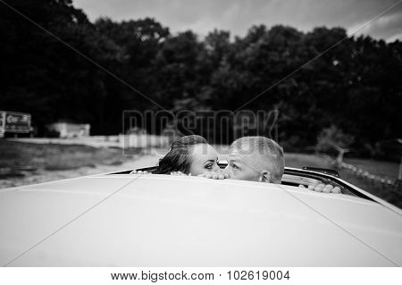 Couple Kissing At The Car Sunroof