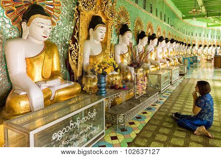SAGAING, MYANMAR, JANUARY 20, 2015 : A woman sitting on the floor is praying Buddha in front of a long row of golden statues in the U-Min Thonze pagoda, Sagaing, Myanmar (Burma)