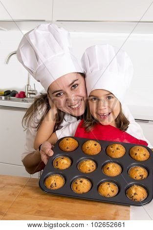 happy mother with little 4 or 5 years old daughter wearing apron and cook hat presenting muffin set after baking together at home kitchen in cooking nutrition and education concept poster
