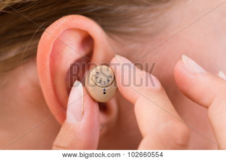 Close-up Of Female Hands Putting Hearing Aid In Ear poster