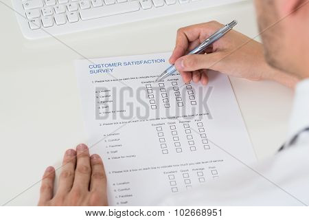 Close-up Of Person Hands Filling Survey Form With Pen poster