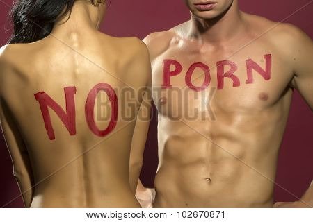 Sexy young undressed couple with no porn message on chest of muscular boy and girl with straight back standing embracing close to each other in studio on purple background vertical photo poster