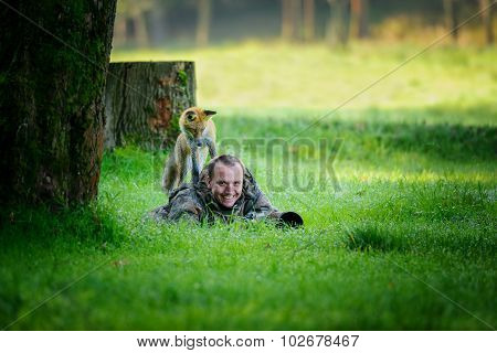 Wildlife Photographer Hidden In Grass With Curious Fox On His Back