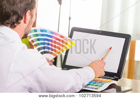 Man working on laptop while holding up palette, colormap from behind angle