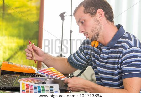 Man wearing blue white striped t-shirt sitting by work desk using phone and looking at palette, colo