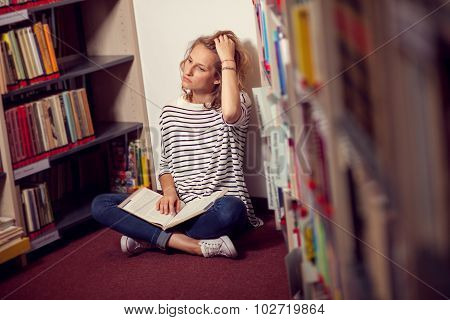 In The Library, Student Girl Or Young Woman With Bookssiting Between Bookstands In The Library.