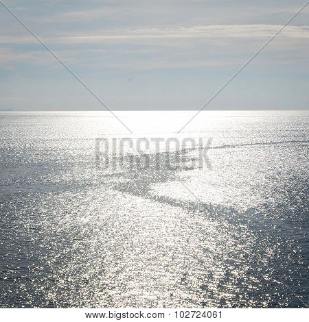 Calm Sea And A Boat Trail. Sunlight On The Water.