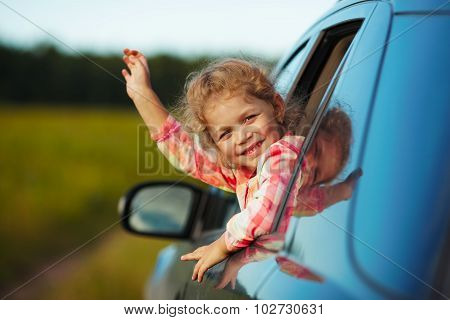 Happy Little Girl Waving From The Car