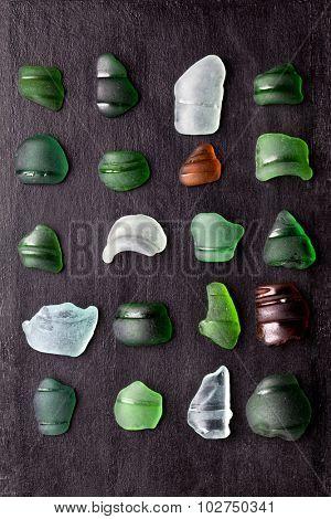 collection of old sea glass bottlenecks on blackboard background