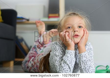 Thoughtful Blonde Little Girl Lying On Floor