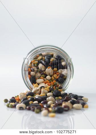 Mix bean of black eye peas, mung bean, adzuki beans, soy beans, black beans and red kidney beans in a mason jar over white background