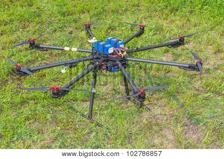 Multicopter standing on the ground in the field poster