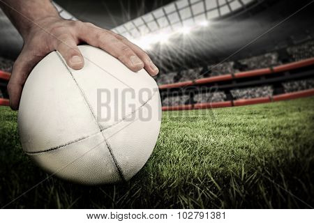 A rugby player posing a rugby ball against rugby stadium