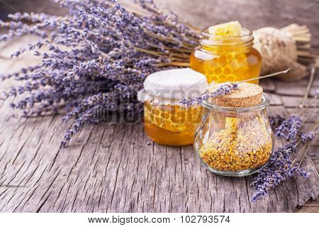 Arrangement of small glass jars with lavender honey, honeycombs and bee pollen with a bunch of dried lavender on dark wooden background. selective Focus poster