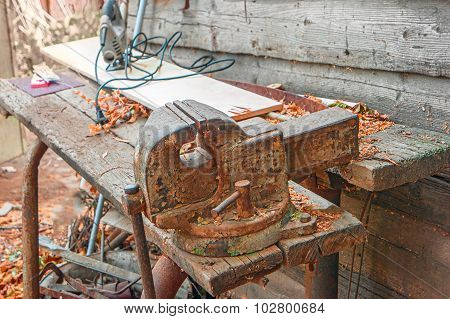 Weathered workbench with rusty metal clumpink device on