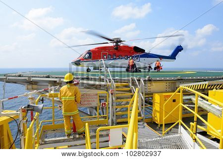 The landing officer are loading baggage of passenger to helicopter at oil rig platform