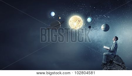 Young man with book exploring planets of sun system