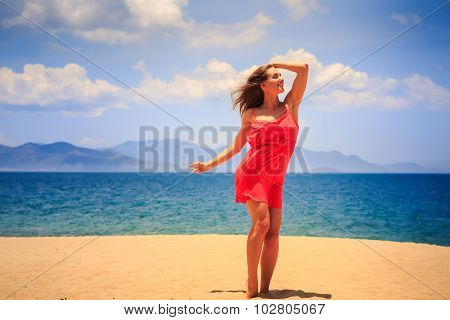 Blond Girl In Red Stands On Sand Touches Head And Looks Upwards