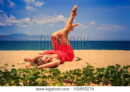 Upper View Girl In Red Lies On Sand Lifts Legs Bends Knees