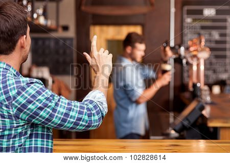 Attractive young guy orders lager in pub
