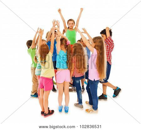 Class leader girl raised hands in circle of mates