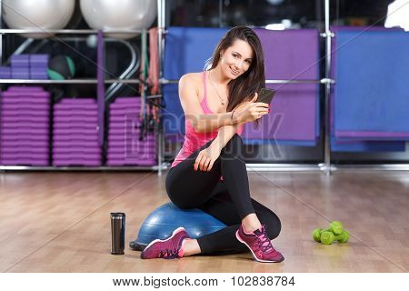 Fitness girl wearing in pink shirt sneakers and black leggings sitting on a bosu ball with smart phone and looking at camera in the gym full body