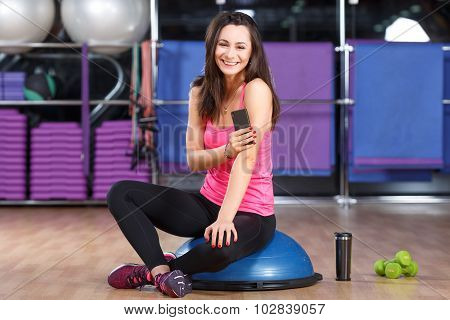 Nice brunette girl wearing in pink shirt sneakers and black leggings sitting on a bosu ball near the cup and dumbbells with smart phone and smiling in the gym full body