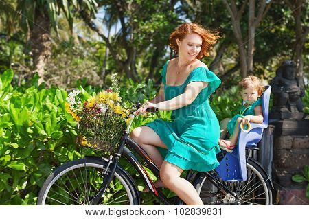 Mother And Daughter Bicycling And Carrying Flowers