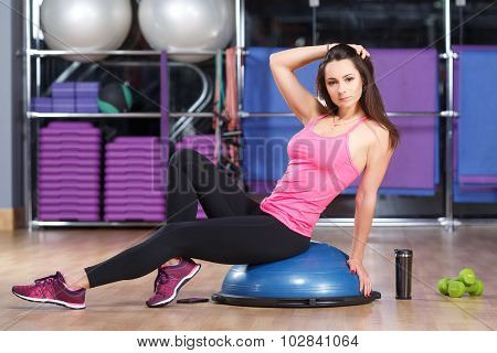 Young brunette woman wearing in shirt sneakers and black leggings posing on a bosu ball cup dumbbells and smart phone lying on the floor in the gym full body
