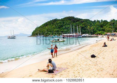 RIO DE JANEIRO, BRAZIL - APRIL 25, 2015: Tourists and sailboat at beach Praia Lopes Mendes on April 25, 2015, Ilha Grande island, Rio de Janeiro state, Brazil.
