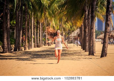 blonde slim girl in short white lace frock runs barefoot between row of palms on beach wind shakes long hair poster