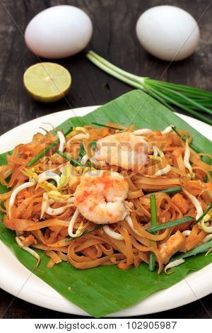 Thai Noodle Or Padthai With  Shrimp And Blur Vegetable,lemon,eggs On Wood  Background.
